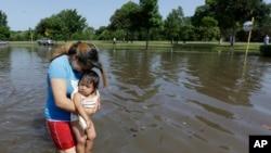 26일 텍사스 휴스턴의 한 아파트가 폭우로 물에 잠긴 가운데 마을 주민이 딸을 안고 범람한 물 속에 서 있다.