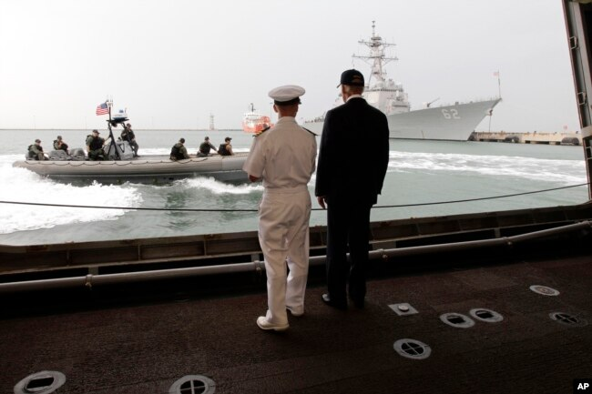 U.S. Vice President Joe Biden, right, watches a maneuver with Cmdr. Tim Wilke, commanding officer of the USS Freedom, the U.S. Navy's first littoral combat ship on rotational deployment at Changi Naval Base, in Singapore Saturday, July 27, 2013.