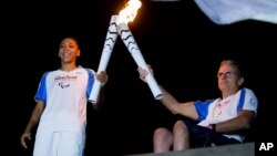 Brazilian judo gold medalist Rafaela Silva, left, and Tomas Magalhaes, member of the Archdiocese of Rio de Janeiro, carry Paralympic torches in front of the Christ the Redeemer statue on its way for the opening ceremony in Rio de Janeiro, Brazil, Tuesday,
