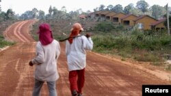 FILE - Women walk past houses, built for the residents being displaced by land sales, at Botum Sakor National Park in Koh Kong province, Feb. 20, 2012.