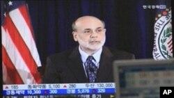 ພໍ່ຄ້າເງິນຕາຄົນນຶ່ງເຮັດວຽກຢູ່ໃນຈໍໂທລະພາບ ທີ່ສະແດງຮູບພາບ ທ່ານ Ben Bernanke ປະທານທະນາຄານແຫ່ງຊາດສະຫະລັດ ທີ່ສໍານັກງານໃຫຍ່ຂອງທະນາຄານແລກປ່ຽນເງິນຕາທີ່ກຸງໂຊນ, ເກົາຫລີໃຕ້ ວັນທີ 10 ສິງຫາ 2011