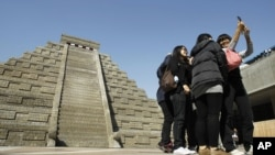 Students take pictures of themselves in front of a mock pyramid during the countdown to when many believe the Mayan people predicted the end of the world, Friday, Dec. 21, 2012, in Taichung, southern Taiwan.