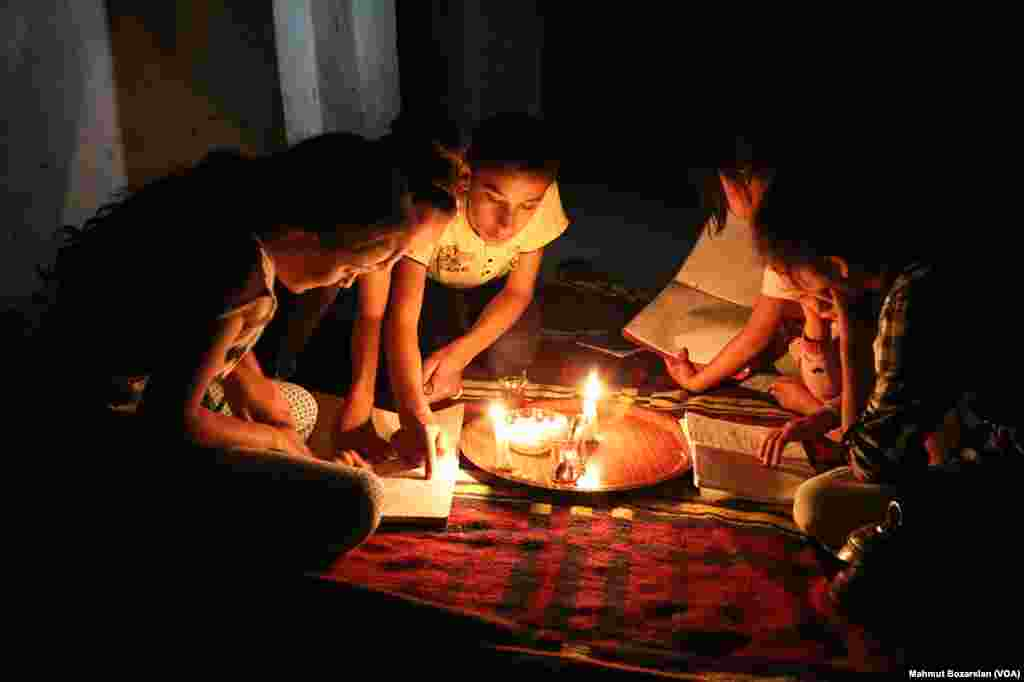 The government has cut power and water to Sur, in Diyarbakir, Turkey, as efforts are made to rebuild it. A family reads by the light of candles inside their home.
