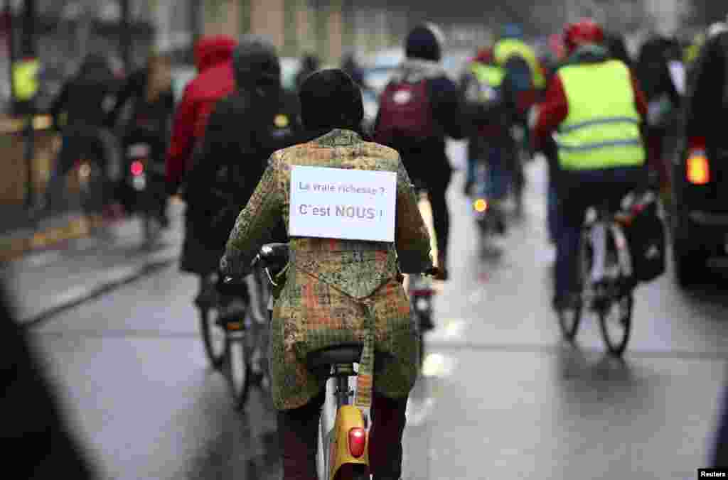 A cyclist wears a sign at Midi/Zuid railway station during a nationwide strike in a protest over the government's planned pension reform and budget cuts, in Brussels, Dec. 15, 2014.