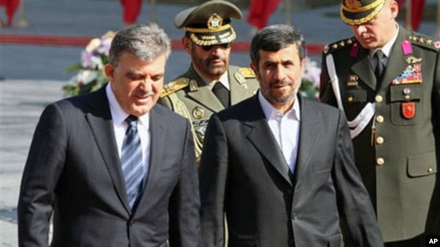 Turkish President Abdullah Gul, left, is welcomed by his Iranian counterpart, Mahmoud Ahmadinejad, during welcoming ceremony for him, in Tehran, Iran, February 14, 2011