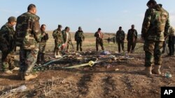 FILE - Kurdish Peshmerga forces inspect a site in Hardan village in northern Iraq where Islamic State fighters allegedly executed people from the Yazidi sect captured when they swept through the area in August.