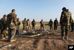FILE - Kurdish Peshmerga forces inspect a site in Hardan village in northern Iraq on Dec. 22, 2014, where Islamic State group fighters allegedly executed people from the Yazidi sect captured when they swept through the area in August.