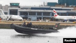 A police dinghy sails past as aircraft stand idle at City Airport after a protest closed the runway causing flights to be delayed, in London, Britain, September 6, 2016.