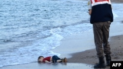 FILE - A Turkish police officer observes the body of migrant child Aylan Shenu on the beach at Bodrum, southern Turkey. Syrians Muwafaka Alabash and Asem Alfrhad were convicted of human trafficking in the deaths of the child and his parents.
