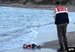 A Turkish police officer stands next to a migrant child's dead body (Aylan Kurdi) off the shores in Bodrum, southern Turkey, on Sept. 2, 2015 after a boat carrying refugees sank while reaching the Greek island of Kos.