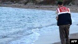 Un policier turc constate la mort d'un enfant syrien au large des côtes à Bodrum, au sud de la Turquie, le 2 septembre 2015. Une image devenue emblématique du drame des migrants en Méditerranée.
