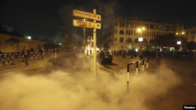 Người biểu tình chạy tránh hơi cay trong vụ đụng độ với cảnh sát trước dinh tổng thống ở Cairo, Ai Cập, 4/12/2012
