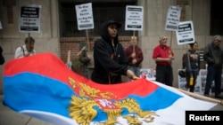 一名抗议者在乌克兰驻纽约领馆前挥舞俄罗斯总统旗。(2014年5月8日)