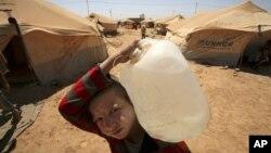 Một bé trai Syria, tị nạn trong trại Zaatari,ở Mafraq, Jordan, mang nước về cho gia đình