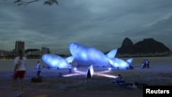 Seorang wanita melintasi ikan raksasa yang terbuat dari botol plastik dan dipamerkan di Pantai Botafogo, Rio de Jenairo (19/6). Konferensi Pembangunan yang Berkelanjutan PBB Rio +20 akan berlangsung di kota ini dari tanggal 20 hingga 22 Juni 2012.