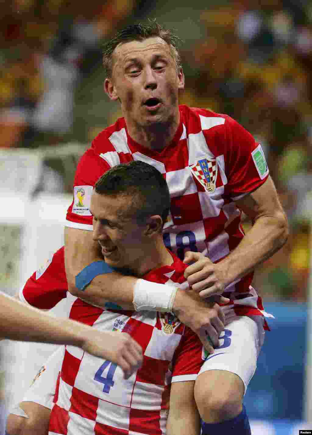 Croatia's Ivan Perisic celebrates after scoring a goal with teammate Ivica Olic (top) during their 2014 World Cup Group A soccer match against Cameroon, at the Amazonia arena, in Manaus, June 18, 2014.