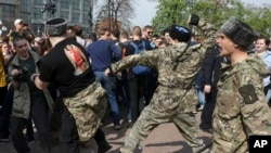 Fighters of National Liberation movement clash with protesters during clashes at a demonstration against President Vladimir Putin in Pushkin Square in Moscow, Russia, Saturday, May 5, 2018.