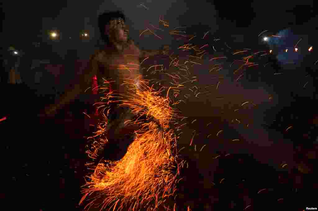 "A Balinese Hindu runs through burning coconut husks during a ""Mesabatan Api"" ritual on the eve of Nyepi, a day of silence for self-reflection to celebrate the new year, in Gianyar, Bali, Indonesia."