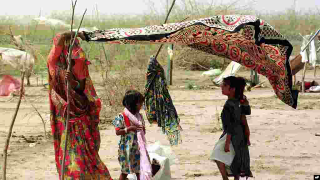 Seorang ibu di distrik Kutch, Gujarat di India, memakai sarinya untuk melindungi anaknya dari panas yang mencapai 50 derajat Celsius pada 2001. Pada 1998, sekitar 2.541 kematian terjadi di India akibat gelombang panas.