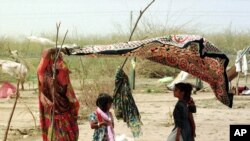 Kanta Solanki utilizes her saree as a form of makeshift shade for her children, to combat the 50 degree Celsius (125 F) heat in the Kutch district of the western Indian state of Gujarat, Monday, May 14, 2001. Solanki's husband was killed in January's ear