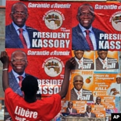 A man puts up electoral posters on a wall in a street of Conakry ahead of Guinea's first free election since independence in 1958.