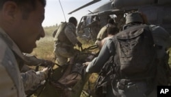 Afghan and U.S. soldiers rush an Afghan soldier, who was wounded in an IED explosion, into a U.S. helicopter (file photo)
