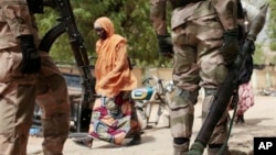 A woman passes Nigerian soldiers at a checkpoint in Gwoza, Nigeria, a town newly liberated from Boko Haram, in this photo dated April 8, 2015. Each month brings new reports of atrocities committed by the militants.