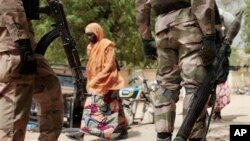 In this photo taken Wednesday, April 8, 2015, a woman walks past Nigerian Soldiers at a checkpoint in Gwoza, Nigeria, a town newly liberated from Boko Haram. Each day brings new reports of atrocities, with mass graves being discovered in towns seized ba