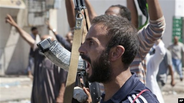 In this Sunday, Aug. 14, 2011 photo, a Libyan rebel fighter in Zawiya, western Libya, reacts to the news that the city of Surman, an important strategic point, is now under the control of the rebel forces.