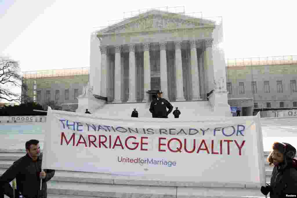 同性婚姻的支持者举着标语站在华盛顿美国最高法院前。最高法院连续第二天听取同性婚姻案,这一次,大法官们听取一项拒绝给予合法结婚的同性伴侣联邦福利的美国法律是否违宪的辩论。