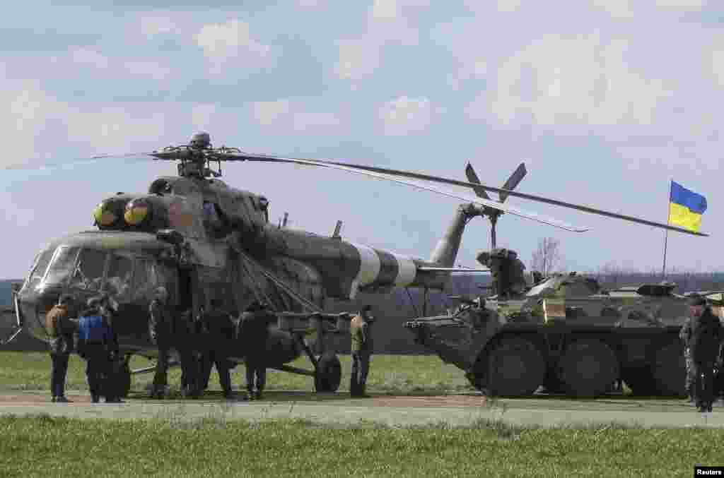 Ukrainian soldiers are seen near a MI-8 military helicopter and armored personnel carrier at a checkpoint near the town of Izium in Eastern Ukraine, April 15, 2014.