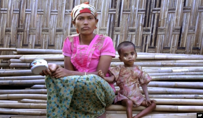 FILE - In this March 17, 2017, image made from video, Rosmaida Bibi, right, who suffers from severe malnutrition, sits with her 20-year old mother Hamida Begum outside their makeshift shelter at the Dar Paing camp, north of Sittwe, Rakhine State, Myanmar.