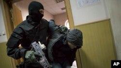 Cảnh sát Nga áp tải một người đàn ông được cho là một trong năm nghi phạm trong vụ giết hại ông Nemtsov vào phòng xử án ở Moscow.