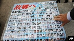 A family member of a South Korean who, he said, was abducted by North Korea, looks at pictures of Japanese people who were believed to be abducted by the North, during a campaign demanding for a legislation of North Korean human rights laws and repatriati