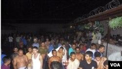 Para tahanan berdiri di halaman penjara, setelah kebakaran besar melanda penjara Comayagua, Honduras, Rabu dini hari (15/2).
