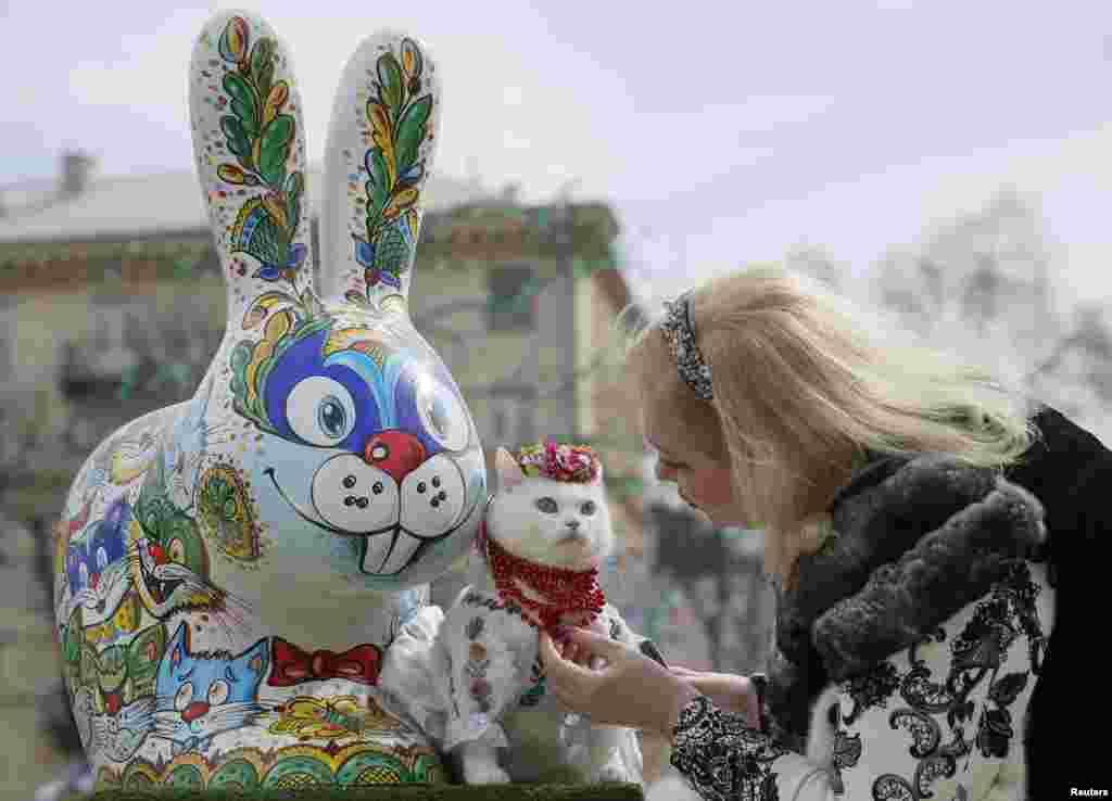 ស្ត្រីម្នាក់ស្លៀកពាក់ឲ្យឆ្មារបស់នាង មុនពេលថតរូបនៅជិតរូបទន្សាយសម្រាប់ពិធី Easter ដែលគេដាក់តាំងនៅក្នុងសួនមួយសម្រាប់ប្រារពពិធីបុណ្យEaster នៅទីក្រុងកៀវ ប្រទេសអ៊ុយក្រែន។