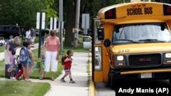 In Wisconsin, teachers watch as pre-school children get on their school bus. (AP Photo/Andy Manis)