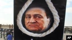 2011年12月28日在埃及首都開羅的一個示威活動中﹐一名示威者高舉將前總統穆巴拉克問吊的畫像。