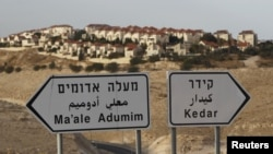 The West Bank Jewish settlement of Maale Adumim, near Jerusalem, is seen behind sign posts December 3, 2012.