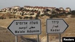在标示牌后面可见耶路撒冷附近约旦河西岸的犹太人定居点