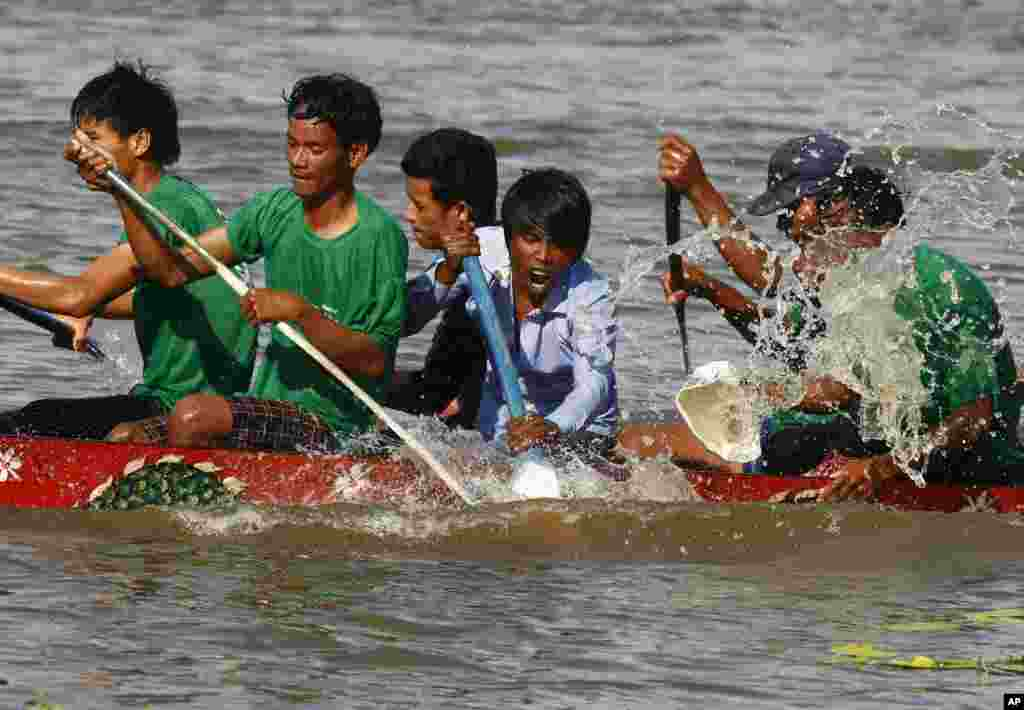 Competitors row their wooden boat during a boat racing as part of celebrations of the Water Festival in Thnol Dach, Takoe province, southwestern Cambodia.