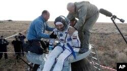 Rusiya fəza agentliyinin işçiləri kosmonavt Anatoli İvanişinə Yerə endikdən sonra Soyuz kapsulundan çıxmağa kömək edir, Jezkazgan, Qazaxıstan