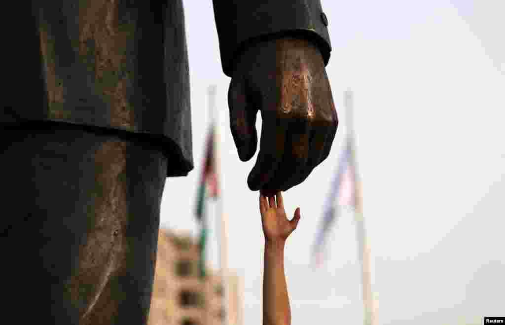បុរសជនជាតិប៉ាឡេស្ទីនមួយរូបស្ទាបរូបសំណាក់លោក Mandela នៅអំឡុងថ្ងៃសម្ពោធទីលាន Nelson Mandela នៅក្រុង Ramallah តំបន់ West Bank កាលពីថ្ងៃទី២៦ ខែមេសា ឆ្នាំ២០១៦។