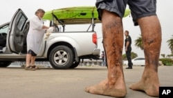 In this photo provided by the Santa Barbara County, Calif., Fire Department, Henry Duncan, left, and Bob Seiler, legs covered in oil, foreground, stand in the Goleta Beach parking lot with their oil-covered kayaks, on the truck at rear, in Goleta, California, Wednesday, July 29, 2015.
