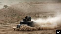 Un véhicule blindé irakienne s'apprêtant à attaquer des miliciens de l'Etat islamique à Tikrit (AP)