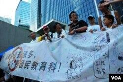 國民教育家長關注組成員展示一幅大橫額,諷刺當局推行國民教育毒害香港學童