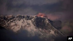 FILE - In this Oct. 27, 2011, photo, the last light of the day sets on Mount Everest as it rises behind Mount Nuptse as seen from Tengboche, in the Himalaya's Khumbu region, Nepal.