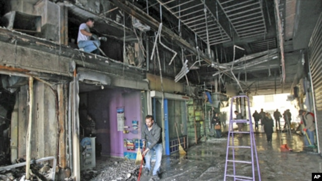 Workers start clean-up operations in a burned out shopping arcade after a night of violence that followed the Greek parliament approval of a deeply unpopular austerity bill in Athens, Greece, February 13, 2012.