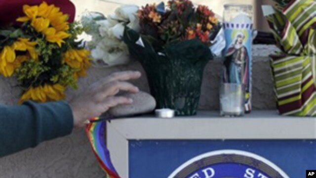 A well-wisher adds an item to a make-shift memorial outside Rep. Gabrielle Giffords' office in Tucson, Ariz., Sunday, Jan. 9, 2011.