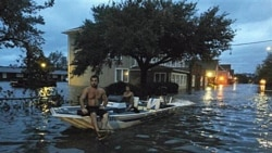 Two men use a boat to get down the street in Manteo, North Carolina Saturday, August 27.